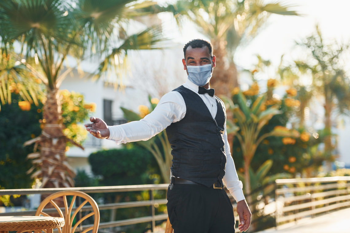In protective mask. Black waiter in formal clothes is at his work outdoors at sunny daytime